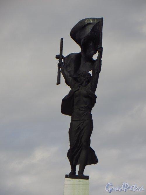 Мемориал «Партизанская слава» на въезде в город лугу со стороны Санкт-Петербурга. Скульптура девушки-партизанки с автоматом и развевающимся знаменем в руках. Фото 22 июня 2014 года.