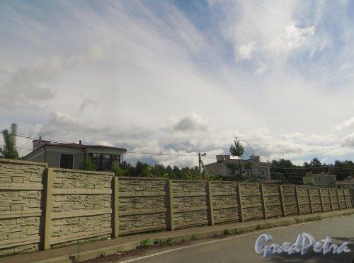 Ограждение коттеджного посёлка «Новый Мир» в сторону коттеджного поселка «Репинская усадьба». Фото 23 июля 2015 года.