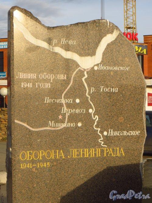 Стелла с надписью «Оборона Ленинграда. 1941–1945» и схемой линии фронта в районе Никольского в 1941 году, установленная на пересечении Советский проспекта и Никольского шоссе, возле рынка в городе Никольское. Фото 26 октября 2014 года.