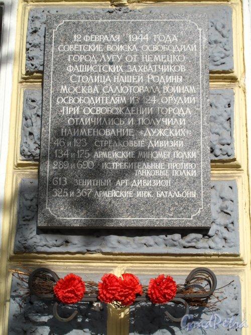 Пр. Кирова, 71. Торгово-офисное здание. Мемориальная доска к дню освобождения Луги: «12 февраля 1944 года Советские войска освободили город Лугу от немецко-Фашистских захватчиков. Столица нашей Родины Москва салютовала воинам освободителям из 124 орудий. При освобождении города отличились и получили наименование «Лужских»: 46 и 123 стрелковые дивизии; 134 и 175 армейские миномётные полки; 289 и 690 истребительные противотанковые полки; 613 зенитный арт. дивизион; 325 и 367 армейские инженерные батальоны». Фото июнь 2014