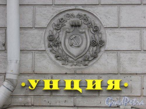 Каменноостровский проспект, дом 2, литера А. Герб СССР с современной рекламой чайного магазина «Унция» на фасаде со стороны сквера. Фото 3 марта 2020 г.