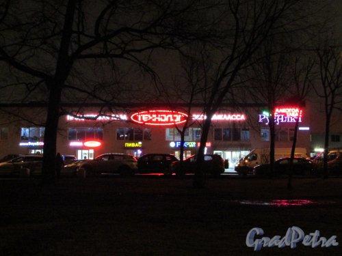 улица Циолковского, дом 10, литера Б. Световая реклама магазинов вечером. Фото 18 декабря 2019 года.