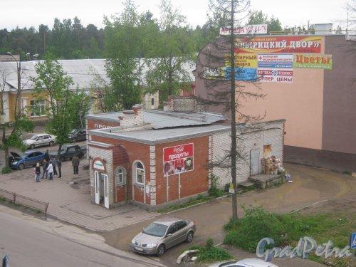 Лен. обл., Гатч. р-н, пос. Вырица (ПГТ). Вид с железнодорожного моста (пешеходный переход над ж/д) на магазины на пересечении Коммунального пр. и ул. 1-го Мая. Фото 25 мая 2013 г.