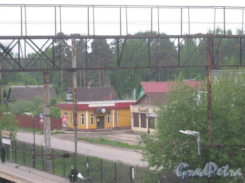 Лен. обл., Гатч. р-н, пос. Вырица (ПГТ). Вид с железнодорожного моста (пешеходный переход над ж/д) на магазины на ул. 1-го Мая. Фото 25 мая 2013 г.