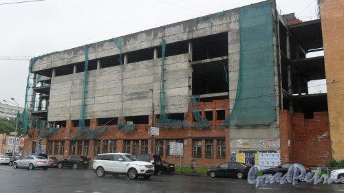 Улица Моисеенко, дом 22, литер О. Недостроенный 4-этажный производственный корпус. Вид здания с Новгородской улицы. Фото 18 июля 2016 года.